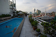 Evening at the roof terrace of Rex Hotel. Guests swimming in the pool with view on City Hall.