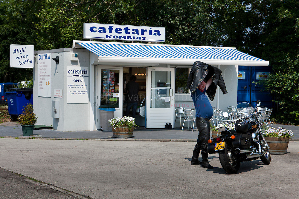 Nederland, Waterhuizen 20120705. Motorrijder trekt zijn jas aan voor cafetaria Kombuis. foto: Pepijn van den Broeke