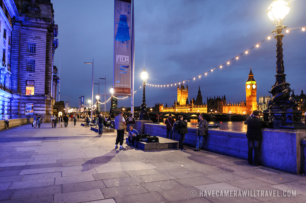 The promenade along the Thames in front of the London Sea Aquarium at dusk. In the background is the Palace of Westminster with Big Ben and the Houses of Parliament.