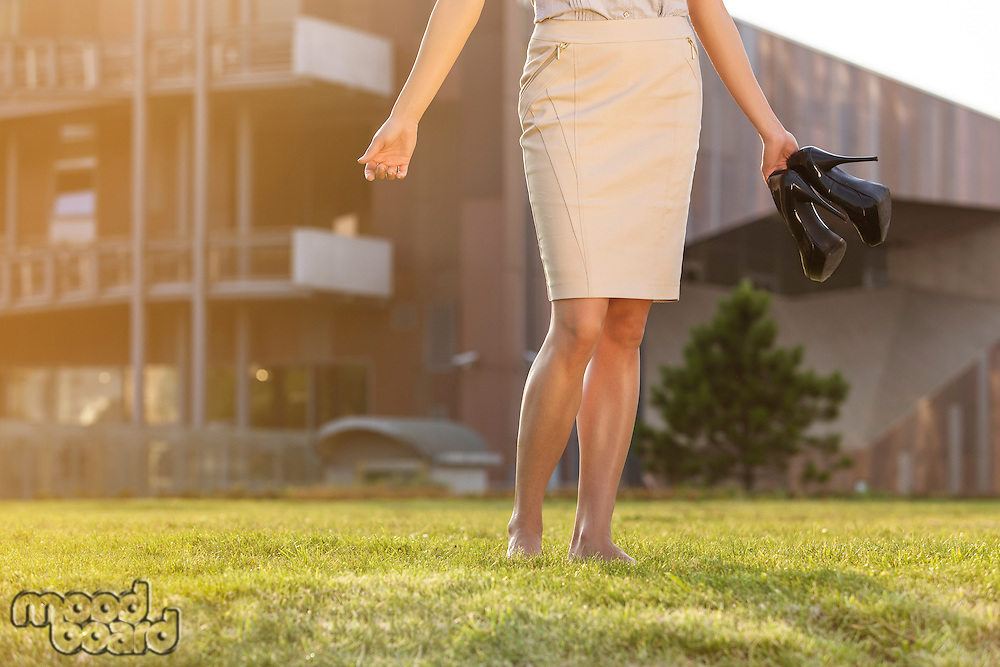Low section of young businesswoman holding footwear in office lawn