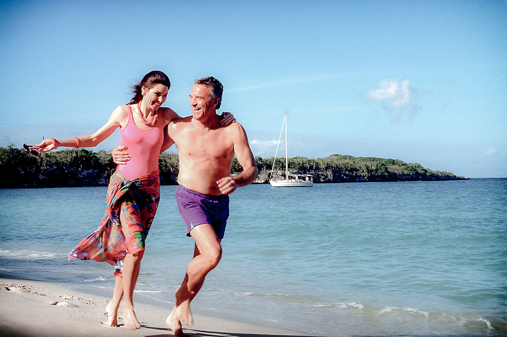 Mature couple playfully running on Caribbean beach, sail boat in background.