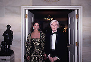 Andy Warhol and date at a State Dinner for the  Shah of Iran on November 15, 1977.<br /> Photo by Dennis Brack