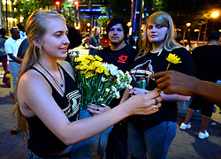 September 23, 2016 - Charlotte, NC, USA - Rachel Rothwell brought flowers to the intersection of Trade and College Streets in Charlotte, N.C., on Friday, Sept. 23, 2016, as demonstrations continue following the shooting death of Keith Scott by police earlier in the week. (Credit Image: © Jeff Siner/TNS via ZUMA Wire)