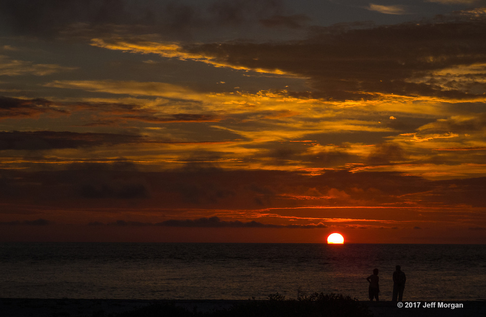 Silhouette of a couple watching the sunset over the Gulf of Mexico.