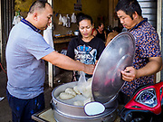 "14 FEBRUARY 2019 - SIHANOUKVILLE, CAMBODIA: A Chinese worker (left) buys steamed buns a Chinese baker (right) who has a shop in the Leu Market in Sihanoukville. The Cambodian woman sells buns to the baker's Cambodian customers. There are thousands of Chinese workers in Sihanoukville who work to support the casino and hotel industry in the town. There are about 80 Chinese casinos and resort hotels open in Sihanoukville and dozens more under construction. The casinos are changing the city, once a sleepy port on Southeast Asia's ""backpacker trail"" into a booming city. The change is coming with a cost though. Many Cambodian residents of Sihanoukville  have lost their homes to make way for the casinos and the jobs are going to Chinese workers, brought in to build casinos and work in the casinos.      PHOTO BY JACK KURTZ"