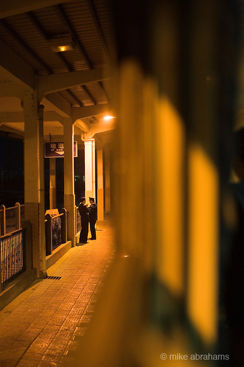 Two guards talking together on the train station platform at night. People's Republic of China