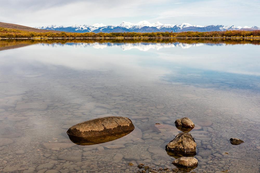 Reflection of Alaska Range in tundra lake along Denali Highway in Southcentral Alaska. Autumn. Morning.