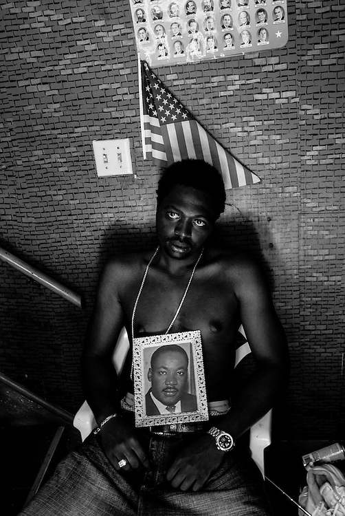 Ryan is pictured, holding a photo of Martin Luther King Jr. and under a poster of past U.S. Presidents, at his home in Gary, Indiana. Ryan was recently let go in a round of layoffs from his job and is struggling to maintain mortgage payments on the home he purchased from his grandmother. (© William B. Plowman/Redux)