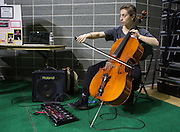 Lily Gelfand, a sophomore BFA dance major in the Honors Tutorial College, demonstrates how to use a loop-pedal system at the Student Expo on April 14, 2016. Gelfand uses the pedal to loop her live cello music during dance classes and performances. Photo by Emily Matthews