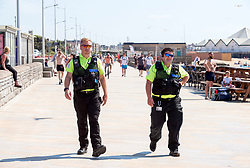 © Licensed to London News Pictures; 02/06/2020; Weston-super-Mare, UK. Two beach wardens patrol on the beach promenade which is quieter on a Tuesday than at the weekend or bank holiday. People at the beach after some lockdown restrictions due to the coronavirus covid-19 pandemic have been lifted by the UK Government. People can spend as long outdoors as they want and can meet in groups of up to six people from different households as long as they maintain social distancing of 2m or more. Photo credit: Simon Chapman/LNP.