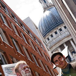 London, UK - 15 June 2012: two protesters holding signs during the Carnival of Dirt with St.Pauls's Cathedral dome in the background. More than 30 activist groups from London and around the world have come together to highlight the illicit deeds of mining and extraction companies.