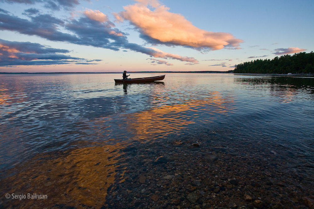 Clouds are reflected on Lake Sebago, Maine as a man paddles a canoe at sunset.