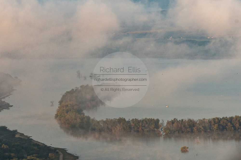 Fog rises over Presa Isabel Allende lake at sunrise as a long fishing boat floats along the water outside the colonial city of San Miguel de Allende, Mexico.