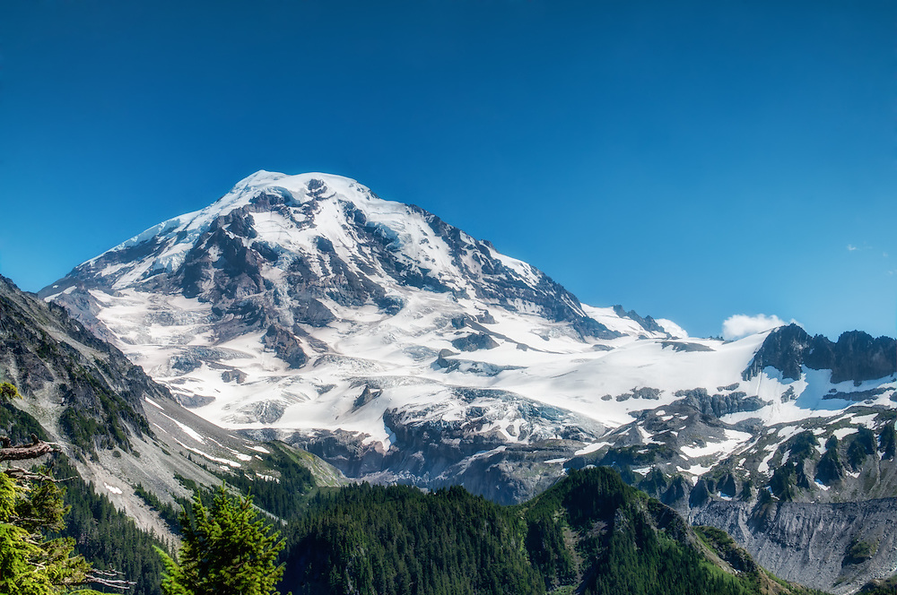 The majestic Mount Rainier towers above the other mountains of Washington state on a hot summer day in early August. This is the north face, photographed at about 4800 feet, just above Spray Creek.