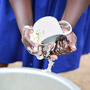CAPTION: Catherine washes an enamel cup by hand. LOCATION: Apapai Parish, Otuboi Sub-county, Kalaki County, Kaberamaido District, Uganda. INDIVIDUAL(S) PHOTOGRAPHED: Catherine Anaso.