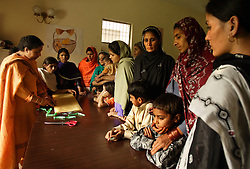 Far right, Shebana, 22, watches a sewing lesson at Dastak, a shelter opened in 1990 for abused women seeking refuge by the AGHA Legal Aid Cell, Lahore, Pakistan, May 2, 2003. Shebana resides at the shelter because her parents disapproved of her wanting to have a love marriage. The boyfriend brought her to the shelter for protection and was later killed by her parents.