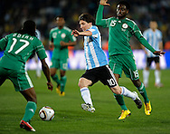 Argentina's forward Lionel Messi (C) controls the ball between Nigeria's defender Chidi Odiah (L) and midfielder Lukman Haruna during the World Cup South Africa 2010 soccer match, at Soccer City stadium, in Johannesburgo, South Africa, on June 12, 2010.  (Alejandro Pagni/PHOTOXPHOTO)