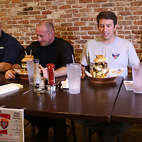 Libby Ezell | BUY AT PHOTOS.DJOURNAL.COM<br /> Sam Warren, left, Eric Grissom, and Joel Young try to make sense of the massive burger that they have to eat for Battle of the Badges
