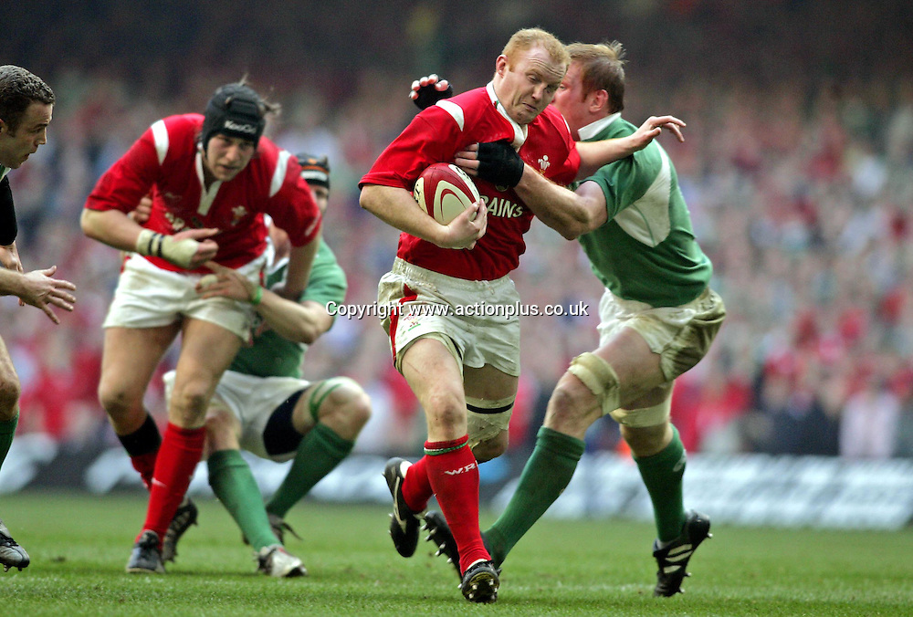 19 March 2005: Welsh flanker Martyn Williams is tackled by Irish lock Paul O'Connell during the RBS Six Nations match between Wales and Ireland. Wales won the match 32-20 to secure their first Grand Slam since 1978. Millennium Stadium, Cardiff, Wales. Photo: Glyn Kirk/Actionplus<br /> <br /> <br /> 050319 player
