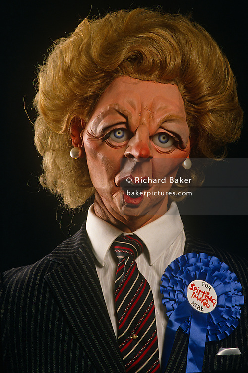 A satirical Margaret Thatcher Spitting Image puppet by Fluck and Law wears a blue Conservative rosette and For Hire sticker.