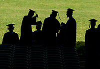 Seniors in silhouette as they begin the 42nd commencement for Gilford High School at Meadowbrook on Saturday morning.  (Karen Bobotas/for the Laconia Daily Sun)