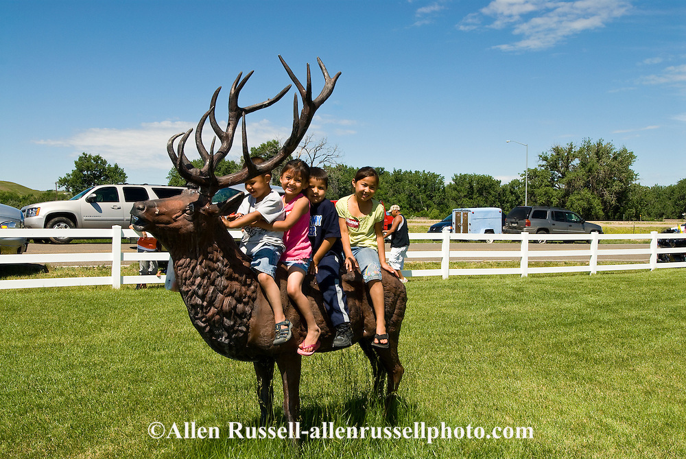 Crow Indian kids play on elk statue in Crow Agency, Montana, Crow Indian Reservation