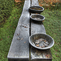 A garden bench and wooden bowls outdoors in winter