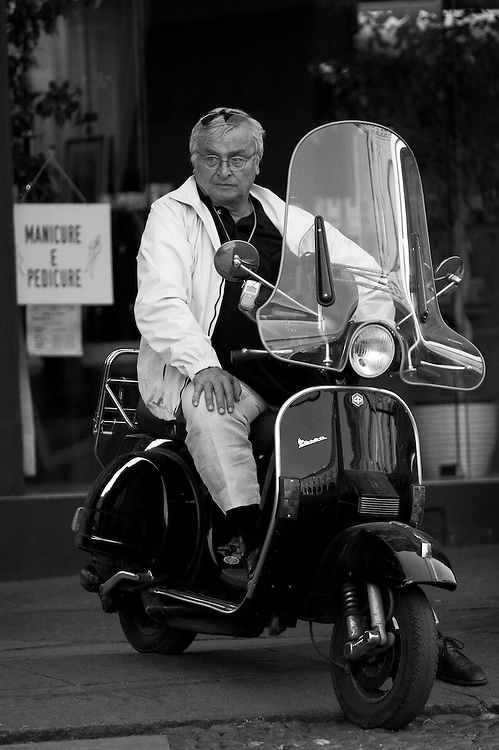 A man sitting on vespa in Bologna Italy.