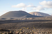 Volcanic landscape of solidified lava flows and distant cone volcanoes, near Yaiza, Lanzarote, Canary Islands, Spain
