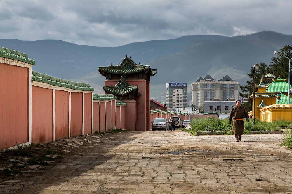 "A Mongolian man walks the grounds of the Gandantegchinlen Monastery, known as the Gandan Monastery, a Tibetan-style monastery in the Ulaanbaatar Mongolian, on July 23, 2012.  The Tibetan name translates to the ""Great Place of Complete Joy."" It currently has over 150 monks in residence. The Gandan Monastery was renovated in 1990 following the collapse of the communist government in Mongolia. © 2012 Tom Turner Photography"