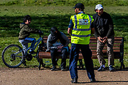 Staff from Lambeth Council patrol with megaphones, gently encouraging visitors not to loiter - A sunny day and people are out in reasonable numbers, on Clapham Common SW London, to get their daily exercise. But in this area the fears of teh police dont seem to have been realised as teh numbers are less than yesterday. The 'lockdown' continues for the Coronavirus (Covid 19) outbreak in London.