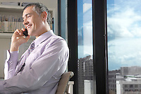 Businessman using mobile phone sitting in front of window overlooking cityscape