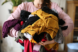 A woman holds a pile of clothes for laundry in a London home. Picture date: Wednesday April 1, 2020.