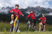 Father with children (7-9) on bikes in countryside portrait