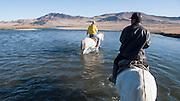 Crossing a river on horseback near Sagsai, Bayan-Ölgii, Mongolia