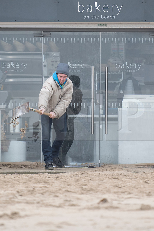 © Licensed to London News Pictures. 02/03/2018. FALMOUTH CORNWALL, UK. Digging the beach sand out from the bakery. Storm Emma caused damage to the beaches and businesses of Falmouth at the morning high spring tide today. The strong wind and the spring tide caused a beach to be washed away at Gylly beach. At Swanpool beach the beach was washed onto the road causing it to be blocked .  Photo credit: MARK HEMSWORTH/LNP
