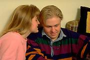 Woman age 18 whispering in boy friends ear.  St Paul  Minnesota USA