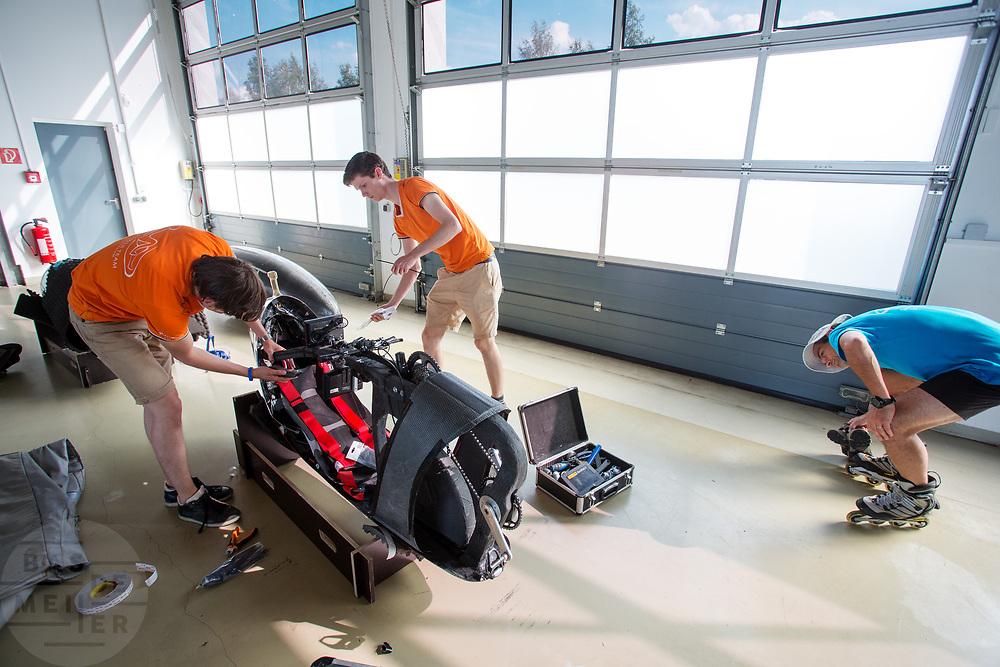 In de werkruimte bij de baan wordt de fiets rijklaar gemaakt, de leider van een ander team bekijkt de fiets. Het Human Power Team Delft en Amsterdam (HPT), dat bestaat uit studenten van de TU Delft en de VU Amsterdam, is in Senftenberg voor een poging het laagland sprintrecord te verbreken op de Dekrabaan. In september wil het Human Power Team Delft en Amsterdam, dat bestaat uit studenten van de TU Delft en de VU Amsterdam, tijdens de World Human Powered Speed Challenge in Nevada een poging doen het wereldrecord snelfietsen voor vrouwen te verbreken met de VeloX 7, een gestroomlijnde ligfiets. Het record is met 121,44 km/h sinds 2009 in handen van de Francaise Barbara Buatois. De Canadees Todd Reichert is de snelste man met 144,17 km/h sinds 2016.<br /> <br /> The Human Power Team is in Senftenberg, Germany to race at the Dekra track as a preparation for the races in America. With the VeloX 7, a special recumbent bike, the Human Power Team Delft and Amsterdam, consisting of students of the TU Delft and the VU Amsterdam, also wants to set a new woman's world record cycling in September at the World Human Powered Speed Challenge in Nevada. The current speed record is 121,44 km/h, set in 2009 by Barbara Buatois. The fastest man is Todd Reichert with 144,17 km/h.