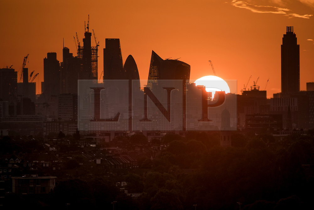 © Licensed to London News Pictures. 21/06/2018. London, UK. The summer solstice sun rises over The City of London at the start of the longest day of the year. A period of hot and sunny weather is forecast for much of the UK over the next 10 days. Photo credit: Peter Macdiarmid/LNP