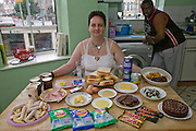 "Jill McTighe, a mother and school aide, with a day's worth of food on a bingeing day, in her kitchen in Willesden, northwest London, United Kingdom.  (From the book What I Eat: Around the World in 80 Diets.) The caloric value of her day's worth of food on a ""bingeing"" day in the month of September was 12300 kcals. The calorie total is not a daily caloric average.  Jill is  31 years old; 5 feet, 5 inches tall;  and 230 pounds. Honest about her food addiction replacing a drug habit, Jill joked about being a chocoholic as she enthusiastically downed a piece of chocolate cake at the end of the photo session. Her weight has yo-yoed over the years and at the time of the picture she was near her heaviest; walking her children to school every day was the sole reason she didn't weigh more. She says this photo experience was a catalyst for beginning a healthier diet for herself and her family. ""Do I cook? Yes, but not cakes. I roast. Nothing ever, ever is fat-fried!"" MODEL RELEASED. [Use of Jill McTighe images must be used contextually only and use cleared with Peter Menzel Photography on a case by case basis.]"