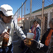 'Attitude at Altitude' Football in Potosi, Bolivia'..Local players enjoy a beer during the finals series at the Liga Deportiva San Cristobal cup finals series on the stone and gravel surface high in the hills over Potosi, as a barbercue is prepared pitch side. Potosi, Bolivia 9th May 2010..'Attitude at Altitude' Football in Potosi, Bolivia'..The Calvario players greet the final whistle with joyous celebration, high fives and bear hugs the players are sprayed with local Potosina beer after a monumental 3-1 victory over arch rivals Galpes S.C. in the Liga Deportiva San Cristobal. The Cup Final, high in the hills over Potosi. Bolivia, is a scene familiar to many small local football leagues around the world, only this time the game isn't played on grass but a rock hard earth pitch amongst gravel and boulders and white lines that are as straight as a witches nose, The hard surface resembles the earth from Cerro Rico the huge mountain that overlooks the town. .. Sitting at 4,090M (13,420 Feet) above sea level the small mining community of Potosi, Bolivia is one of the highest cities in the world by elevation and sits 'sky high' in the hills of the land locked nation. ..Overlooking the city is the infamous mountain, Cerro Rico (rich mountain), a mountain conceived to be made of silver ore. It was the major supplier of silver for the spanish empire and has been mined since 1546, according to records 45,000 tons of pure silver were mined from Cerro Rico between 1556 and 1783, 9000 tons of which went to the Spanish Monarchy. The mountain produced fabulous wealth and became one of the largest and wealthiest cities in Latin America. The Extraordinary riches of Potosi were featured in Maguel de Cervantes famous novel 'Don Quixote'. One theory holds that the mint mark of Potosi, the letters PTSI superimposed on one another is the origin of the dollar sign...Today mainly zinc, lead, tin and small quantities of silver are extracted from the mine by over 100 co operatives and priva