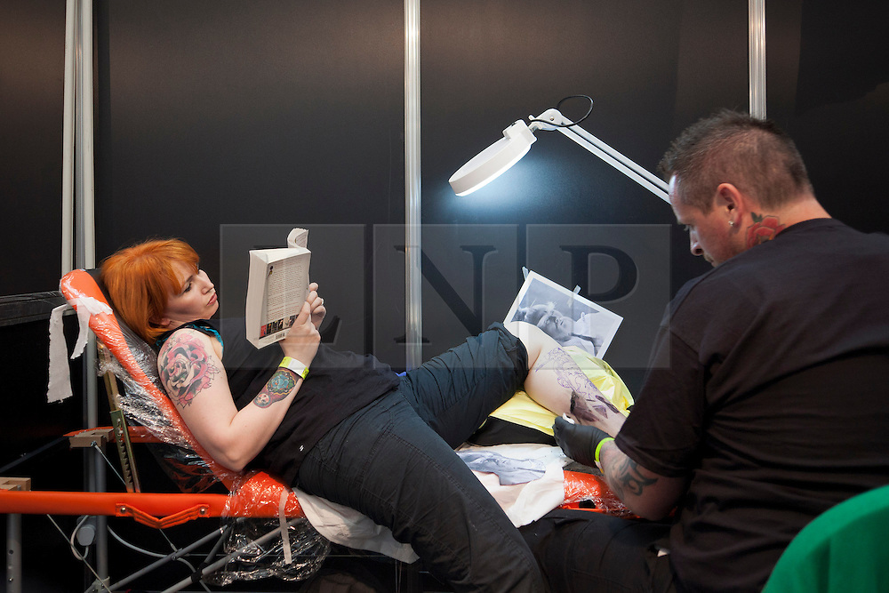 © Licensed to London News Pictures. 25/05/2013. London, UK. A woman reads a book whilst a tattoo artist works on a tattoo on her leg at the Great British Tattoo Show in Alexandra Palace in London today (25/05/2013). The event, which began last year, brings tother world-class tattoo artists artists, vendors and traders and this year takes place on the 25th and 26th of May 2013. Photo credit: Matt Cetti-Roberts/LNP