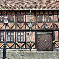 FaxelHuset Half-timbered Façade in Malmö, Sweden<br /> This delightful half-timbered building in the Gamla Staden or old district of Malmö is the FaxelHuset. Proudly over the door the Faxeska house displays the year when it was constructed in 1580 and then rebuilt in 1846 and 1910. Above those dates is a sign decorated with grape bunches. This is a reference to when the Faxe brothers ran a successful wine business here called Adolf Faxe & Sons. The building is still owned by members of that family.