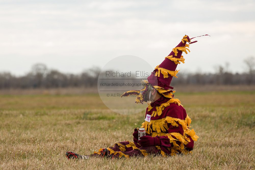 A costumed reveler rests during the Faquetigue Courir de Mardi Gras chicken run on Fat Tuesday February 17, 2015 in Eunice, Louisiana. The traditional Cajun Mardi Gras involves costumed revelers competing to catch a live chicken as they move from house to house throughout the rural community.