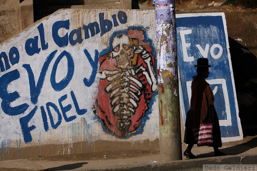 "An indigenous woman walks by graffiti supporting presidential candidate President Evo Morales in La Paz, Monday, Nov. 30, 2009.  Bolivia will hold general elections on Dec. 6.  The graffiti reads in Spanish ""I join the change, Evo and Fidel"" referring to Evo Morales for president and Fidel Surco for senator."