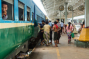 15 JUNE 2013 - YANGON, MYANMAR: Passengers board a Yangon Circular Train. The Yangon Circular Railway is the local commuter rail network that serves the Yangon metropolitan area. Operated by Myanmar Railways, the 45.9-kilometre (28.5mi) 39-station loop system connects satellite towns and suburban areas to the city. The railway has about 200 coaches, runs 20 times and sells 100,000 to 150,000 tickets daily. The loop, which takes about three hours to complete, is a popular for tourists to see a cross section of life in Yangon. The trains from 3:45 am to 10:15 pm daily. The cost of a ticket for a distance of 15 miles is ten kyats (~nine US cents), and that for over 15 miles is twenty kyats (~18 US cents). Foreigners pay 1 USD (Kyat not accepted), regardless of the length of the journey.     PHOTO BY JACK KURTZ