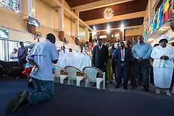 3 November 2019, Monrovia, Liberia: Rev. Eddie Gibson kneels before his congregants during Sunday service at the Providence Baptist Church, also known as 'the cornerstone of the nation', as it was in the Providence Baptist Church that Liberia's declaration of independence was signed. While this Sunday service is taking place in a larger worship space finalized in 1976, the old chapel remains in place adjacent to the new one, and is still in use.