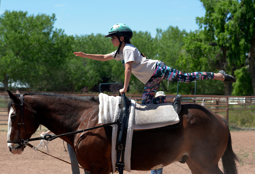 "gbs050717m/LIVING -- Esmeralda  ""Esme""  Marquez-Chavez, 9, of Albuquerque, performs a horse vaulting freestyle program during practice at Cloud Dancers of the Southwest Therapeutic Horsemanship stables. (Greg Sorber/Albuquerque Journal)"