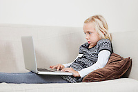 Side view of young girl using laptop on sofa