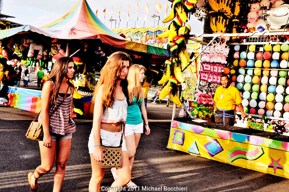 EAST RUTHERFORD, NJ - July 01:  Three girls pass a game booth at the State Fair at the New Meadowlands Fairgrounds on July 01, 2011 in EAST RUTHERFORD, NJ.  The first Fair at the Meadowlands opened in 1986 as a 6-day event encompassing 10 acres offering a dozen rides and games. Today State Fair Meadowlands at Giants Stadium Fairgrounds is the largest in New Jersey and in the NY Metro area encompassing 35 acres, featuring over 150 rides and attractions plus over 75 food vendors from around the country.  (Photo by Michael Bocchieri/Bocchieri Archive)